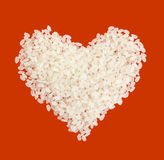 Rice grains in  form of heart on a red background Royalty Free Stock Images