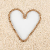 Rice grains and a rope in the shape of a heart with a place for designers. Royalty Free Stock Photography