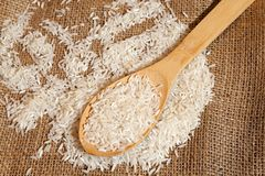 Rice grains on a wooden spoon Stock Image