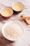 Rice, green tea and chopsticks for sushi on white wooden backgro Stock Images