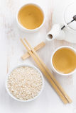 Rice, green tea and chopsticks for sushi on white Royalty Free Stock Photography