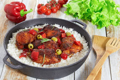 Rice with grilled chicken thighs, red bell pepper, green olives. And rosemary in cast iron stewpan on white old wooden table, vegetables and lettuce on stock images