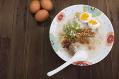 Rice gruel and eggs. On table Stock Photography