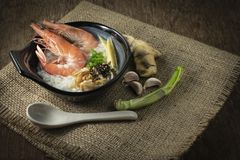 Rice gruel mixed with prawn and ginger, scallion slice and deep fried garlic and black pepper in black bowl. spices put right side royalty free stock photo