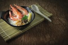 Rice gruel mixed with prawn and ginger, scallion slice and deep fried garlic and black pepper in black bowl. ceramic spoon put royalty free stock images