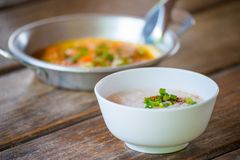 Rice gruel and panned egg on wooden table. Thai breakfast Royalty Free Stock Images
