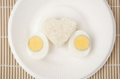 Rice heart and egg on white plate Royalty Free Stock Images