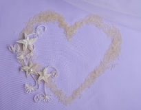 Rice heart and macrame flowers. On violet background for wedding invitations Stock Photos