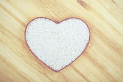 Rice. With heart shape on a wooden table Royalty Free Stock Image