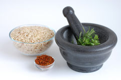 Rice with Herbs. Freshly picked oregano and fresh rosemary in a gray mortar, a bowl of wholegrain rice  and dry saffron on a white background Stock Photos