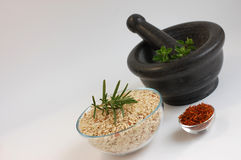 Rice with Herbs. Freshly picked oregano in a gray mortar, a bowl of wholegrain rice with fresh rosemary and dry saffron on a white background Stock Photos