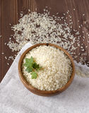 Rice with herbs in a wooden plate on linen napkin. Uncooked rice in wooden plate on linen napkin Stock Images