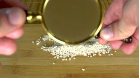 Rice increase grits under a large glass of spoon on a board with a brown background