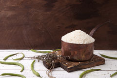 Rice in iron stewpan with green beans on wooden cutting plank. Copy cpace for text Stock Photo
