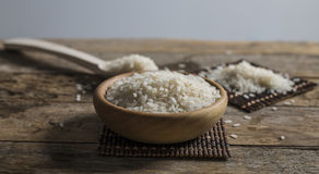 Rice, jasmine rice, mali rice in Ladle and basket on the wood background Royalty Free Stock Photo