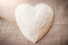 Rice laid out in a heart shape on sackcloth Stock Photos