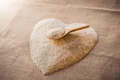 Rice laid out in a heart shape on sackcloth with wooden spoon Royalty Free Stock Image