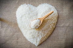 Rice laid out in a heart shape on sackcloth with wooden spoon Royalty Free Stock Photo