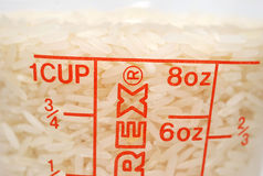 Rice measure. One cup of uncooked rice in container Stock Photo