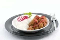 Rice and meat balls. White rice plated with meat balls in a roasted pepper sauce with a decorative radish for a garnish.j stock images