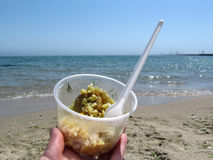 Rice with meat close-up on the sea shore. A female hand holds a takeaway food in a plastic disposable tableware on the beach. Concept of fast food takeaway Royalty Free Stock Images