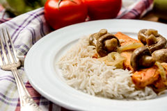 Rice with meat and mushrooms in white plate on tovel Royalty Free Stock Photography
