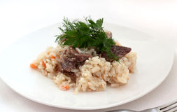 Rice with meat. Rice with meat on a white plate. Horizontal photo. Gray background Stock Photo