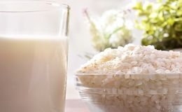 Rice milk and rice in containers in kitchen close up Stock Image