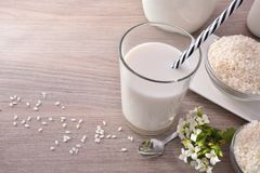 Rice milk and rice in containers in rustic kitchen elevated Royalty Free Stock Image