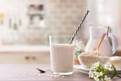 Rice milk and rice in containers in rustic kitchen front Royalty Free Stock Photo