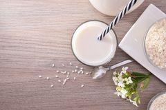 Rice milk and rice in containers in rustic kitchen top Stock Image