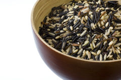 Rice mix - bown, wild, basmati. A wooden bowl of brown, wild, basmati rice mix against white background Stock Photos