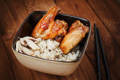 Rice with mushrooms and baked chicken wings Stock Photo