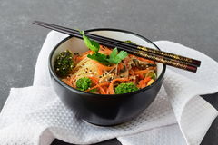 Rice noodles with carrot, broccoli and mushrooms in a black bowl on a black abstract background. Asian food. Healthy Stock Photos