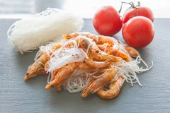 Rice noodles - cellophane boiled shrimp on the grill, spices and tomatoes. The Asian kitchen. royalty free stock image