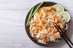 Rice noodles with chicken, shrimp and vegetables top view Royalty Free Stock Photos