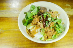 Rice noodles dressing spicy minced pork and bone red cotton tree sauce with vegetable on bowl Stock Photo