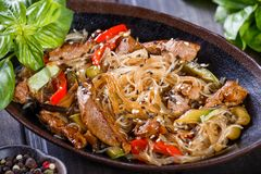 Rice noodles with meat, vegetables and sesame seeds on wooden table. Indian cuisine. Top view stock image