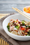 Rice noodles with peas and onions in a white bowl Stock Image