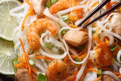 Rice noodles with seafood and chicken, vegetables macro Stock Photos