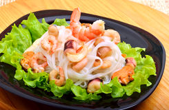 Rice noodles with seafood, olives and green salad on black plate Royalty Free Stock Images