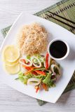 Rice noodles and vegetable salad with squid vertical top view Stock Image