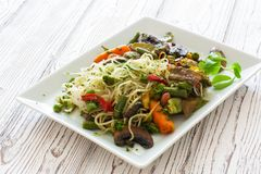 Rice noodles with vegetables and mushrooms. Served on a white plate Royalty Free Stock Image