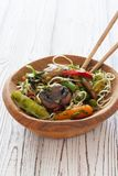 Rice noodles with vegetables and mushrooms. Served on a wood plate Stock Images