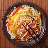 Rice noodles with vegetables on a plate close-up. top view Stock Images