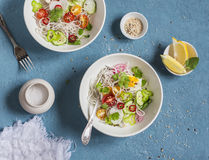 Rice noodles and vegetables salad. Healthy vegetarian food. On a blue background Stock Photos