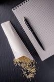 Rice, notebook, dark board. Royalty Free Stock Image