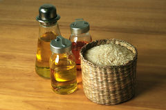 Rice and Oil. In different types of containers on a wooden table Stock Image
