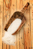 Rice in an old wooden scoop on table Royalty Free Stock Images