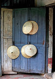 Rice picker hats on blue door. Rice picker hats hanging on blue grunchy door Royalty Free Stock Image